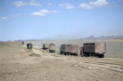 Trucks used in the mines driving across the steppe